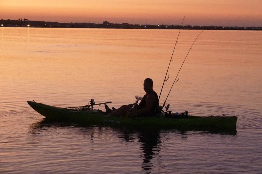 angler fishing from kayak in sunset on lake