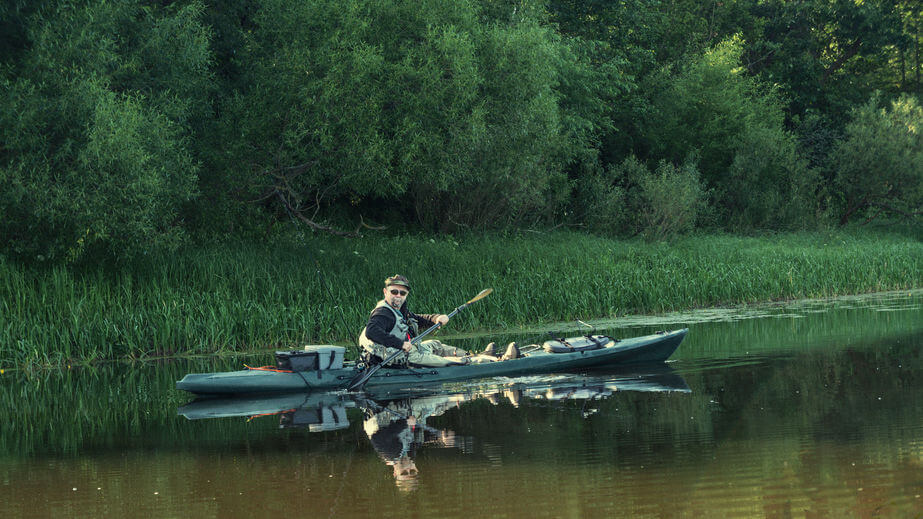 angler fishing on the kayak in river