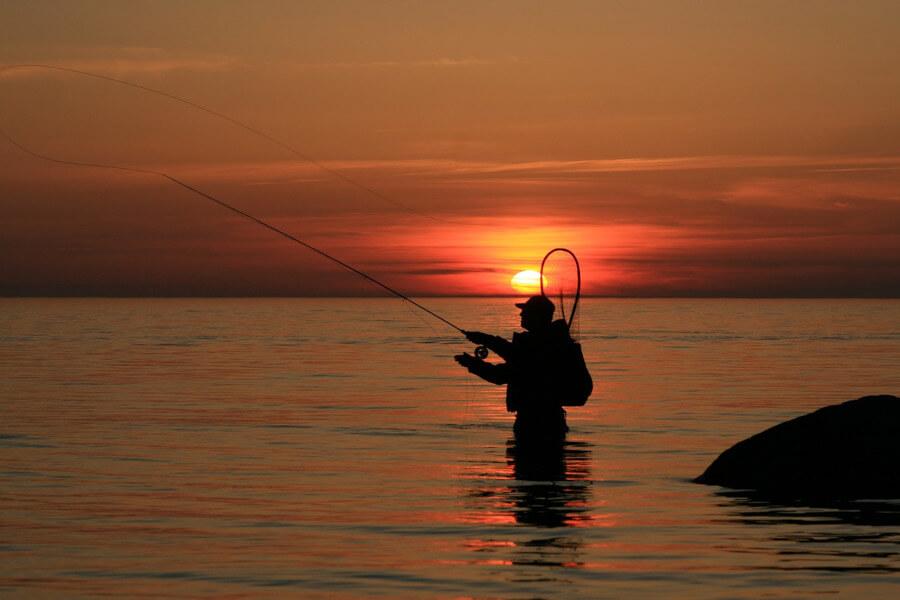 angler fly fishing at sunset