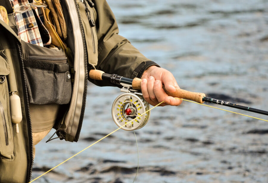 angler fly fishing in river