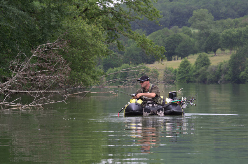 angler fly fishing with a float tube in river