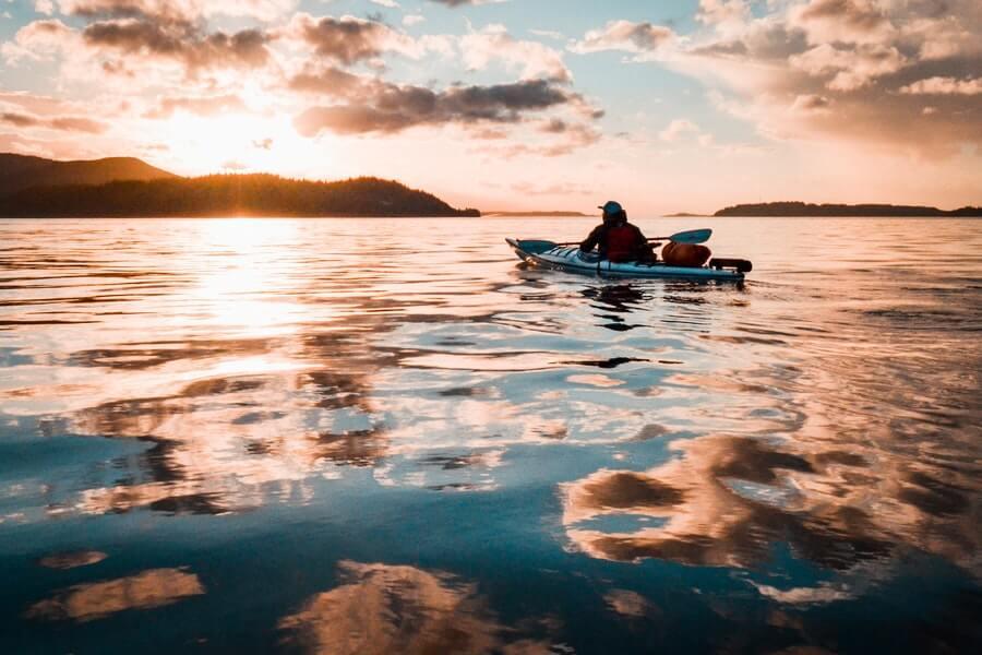 angler sitting on fishing kayak on calm water of river