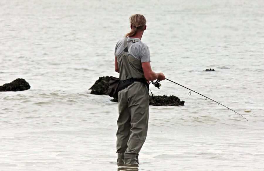 angler wearing chest waders and fishing in sea
