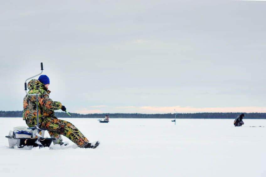 angler wearing warm ice fishing suit and catches a fish in the winter