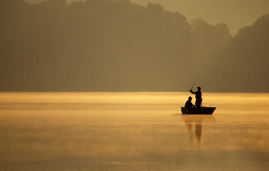 anglers enjoy a beautiful, golden, misty morning fishing on a lake