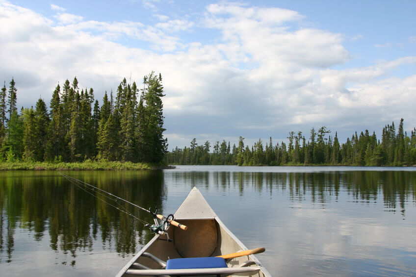 canoe with fishing gear heading out on lake