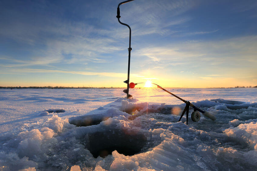 close-up ice auger drill and fishing rod near the hole on the ice