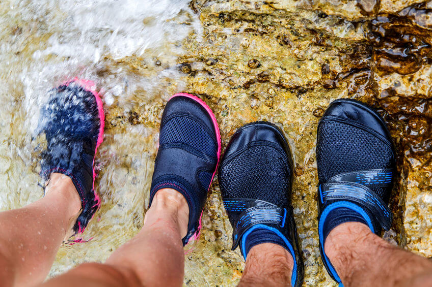 couple wearing water shoes and standing on rocky beach