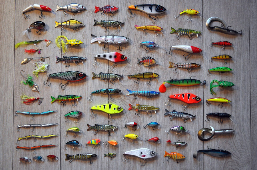 different types of fishing lures on wooden background