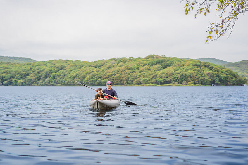 father and son kayaking on the sea