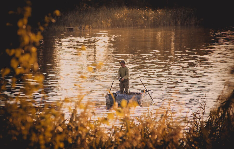 fisherman fishing from boat with spinning rod