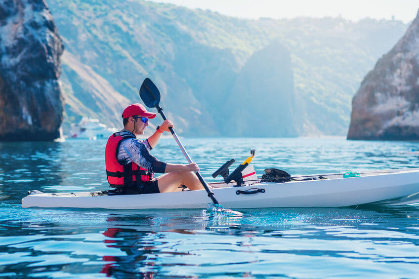 fisherman floats on a white fishing kayak in ocean along the coast