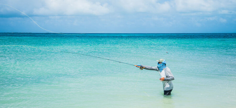 fisherman fly fishing in ocean from beach