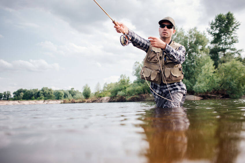 fisherman fly fishing in river