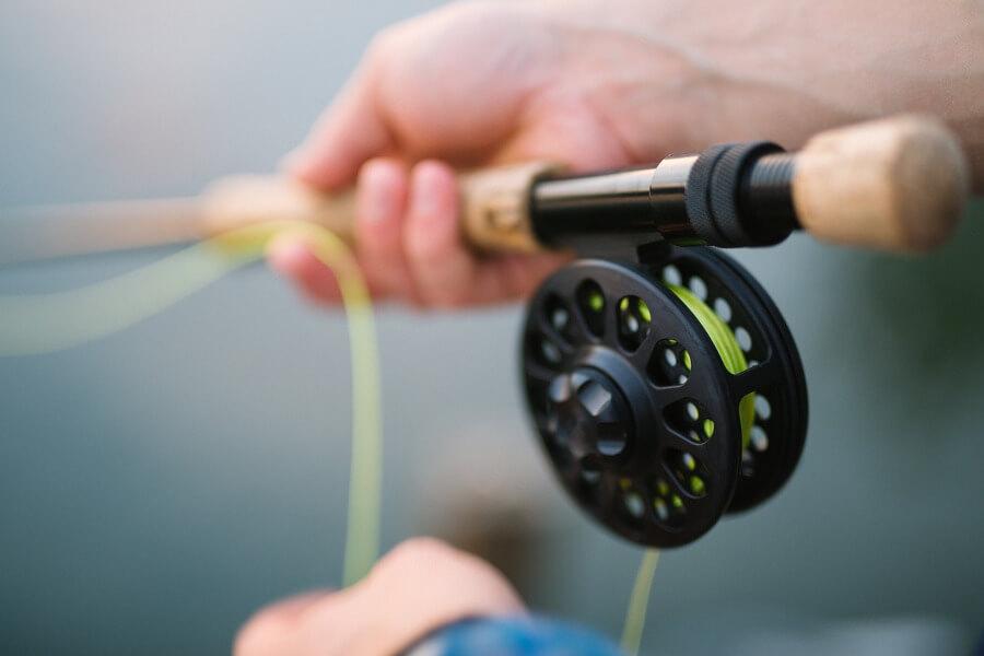 fisherman holding fly fishing rod