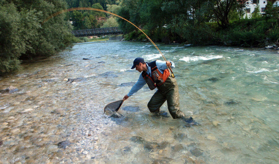 fisherman holding net and fly fishing in river