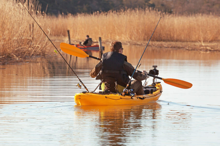 fisherman in sit-on-top kayak with multiple fishing rods