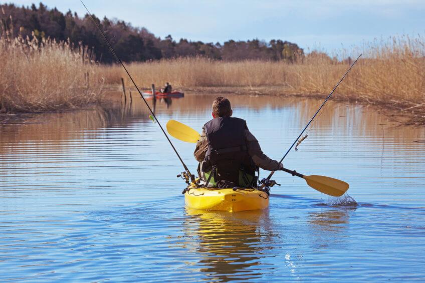 fisherman in small sit-on-top fishing kayak on river