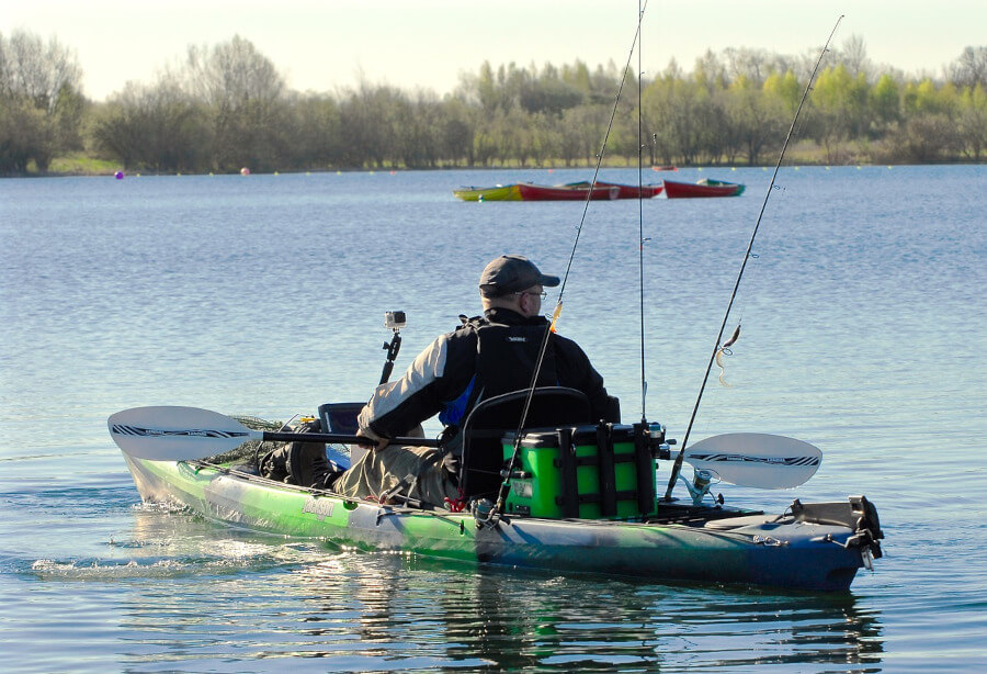 fisherman kayaking and fishing on lake