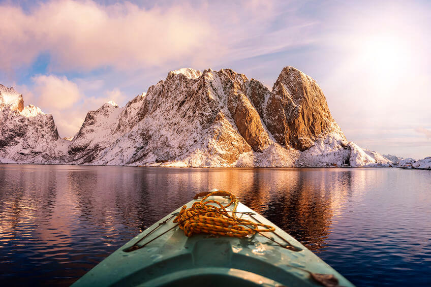 fisherman kayaking on a lake near snow capped mountains in winter