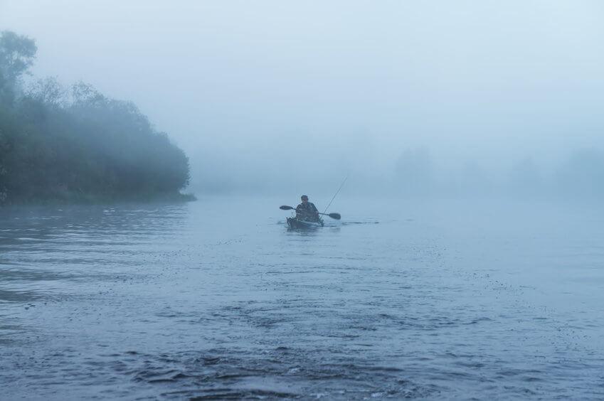 fisherman kayaking on the lake