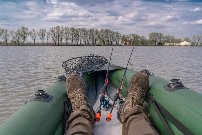 fisherman on inflatable fishing kayak with fishing tackle
