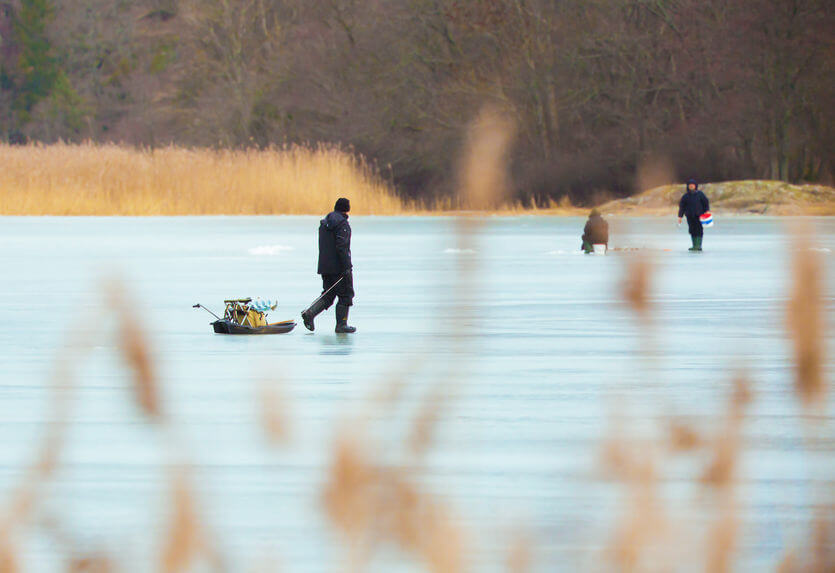 fisherman on the ice on the frozen lake with his equipment in a sled