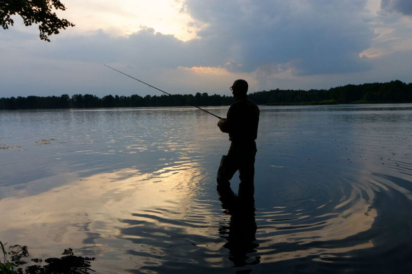 fisherman standing in the lake and catching the fish during rain