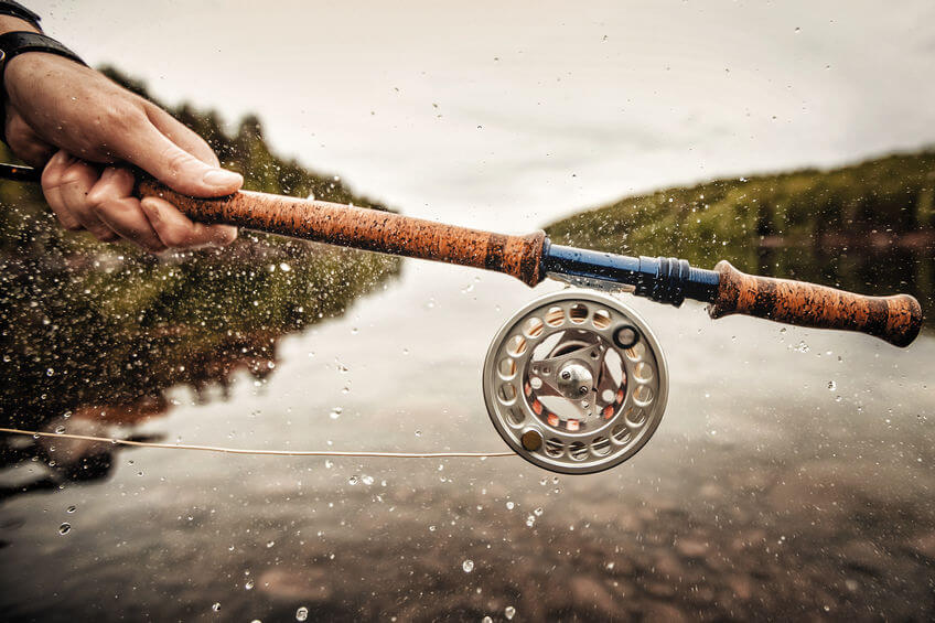 fisherman using fly fishing rod and reel in mountain river