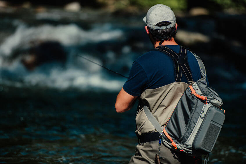 fisherman wearing chest wader and sling pack fly fishing in river