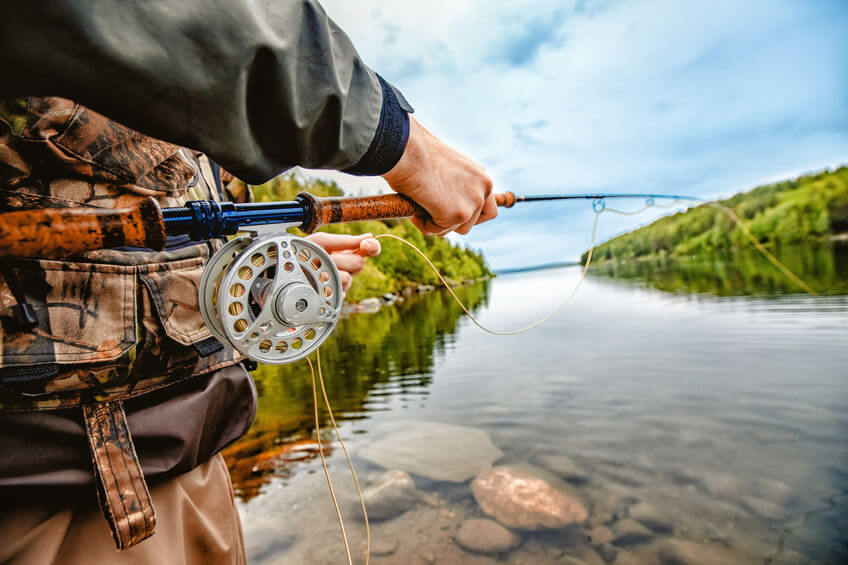 fisherman wearing fishing vest and using rod fly fishing in river