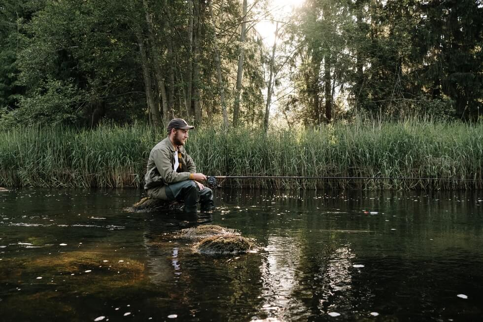 fisherman wearing wader jacket and hat fishing in river