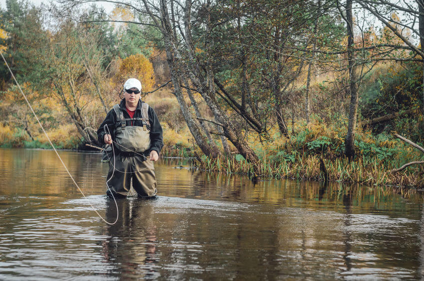 fisherman wearing waders and sunglasses fly fishing in river