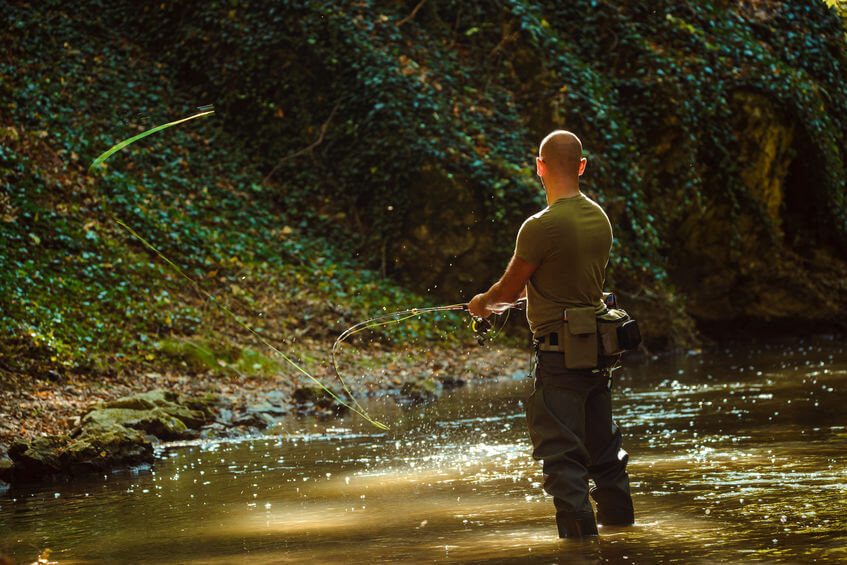 fisherman wearing waist pack and fly fishing in river