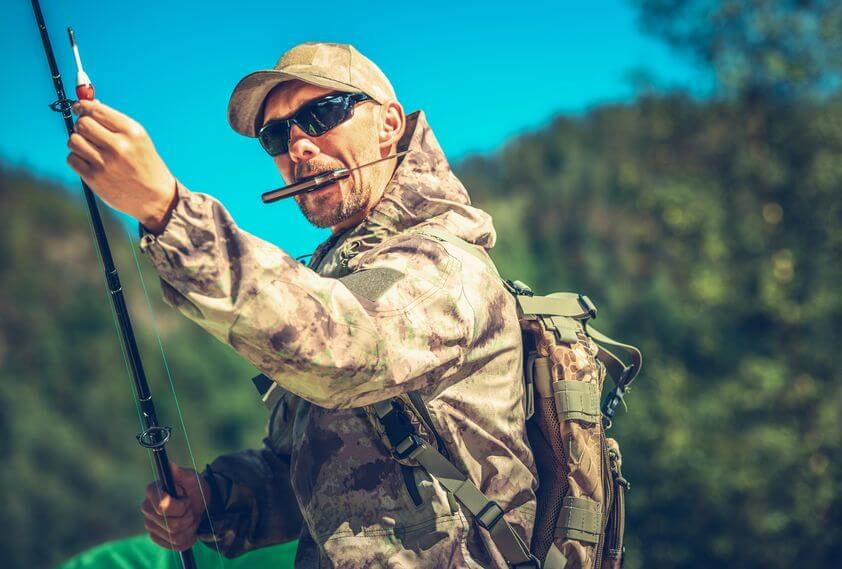 fisherman with folding knife in mouth and holding rod preparing for a fly fishing