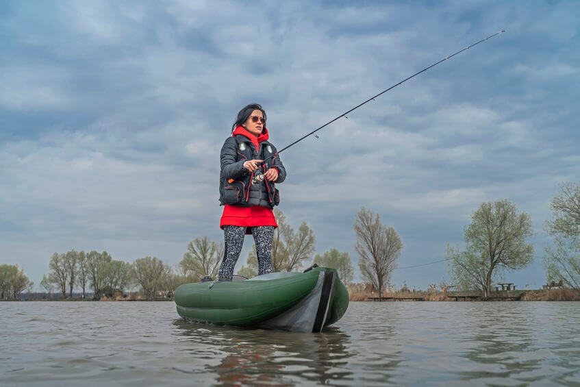 fisherwoman standing on inflatable kayak with fishing tackle