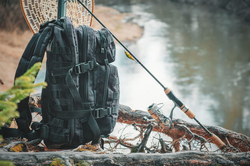 fishing backpack and rod close-up on the riverbank