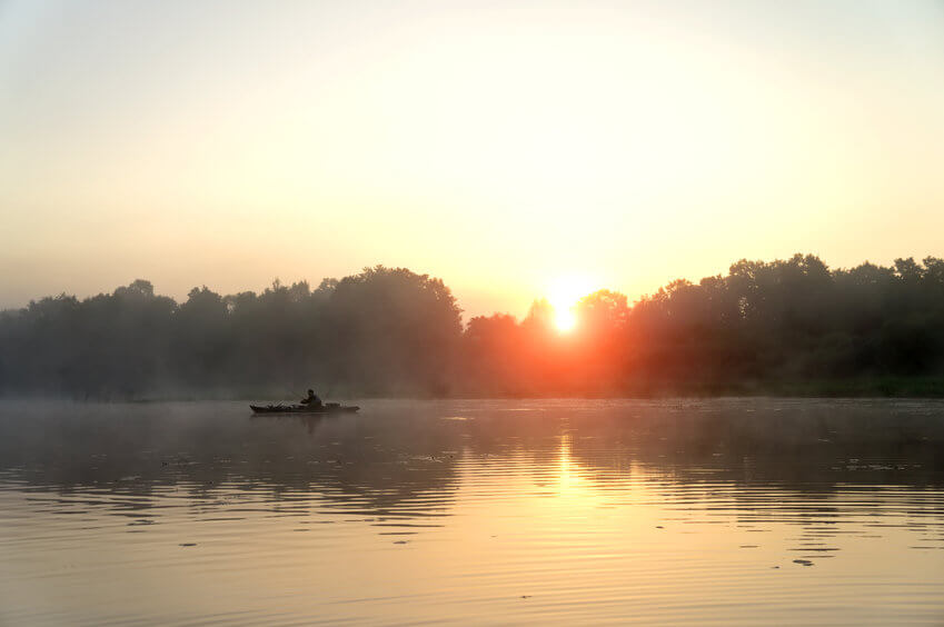 fishing on a river bank from kayak in the morning