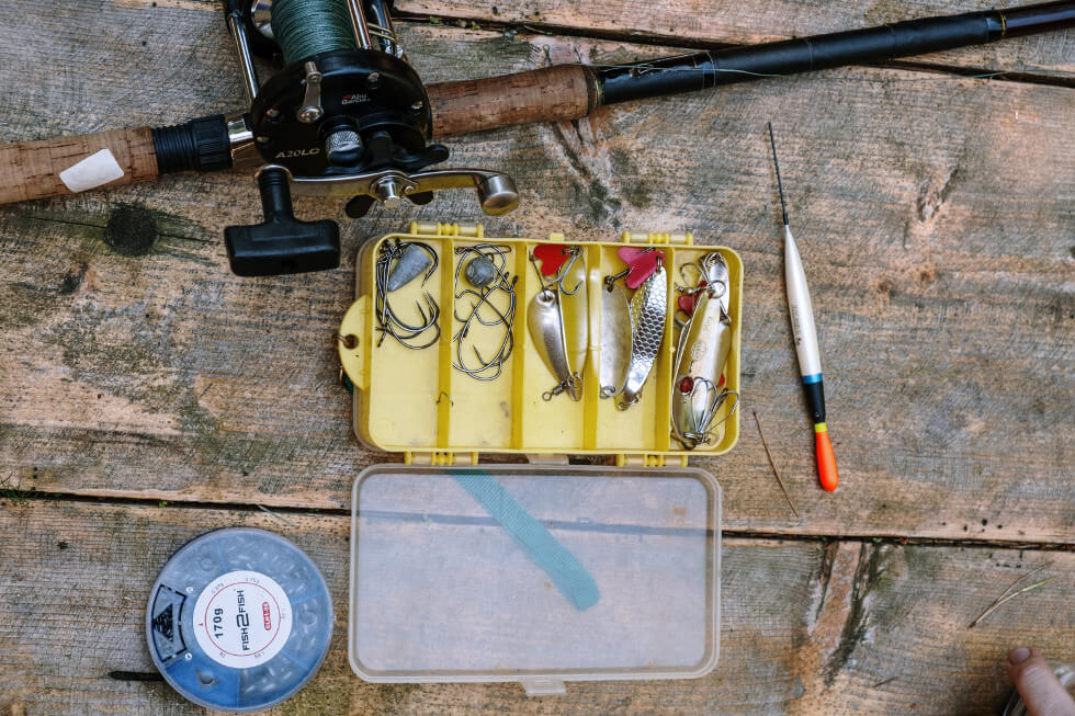 fishing rod and yellow tackle box on table