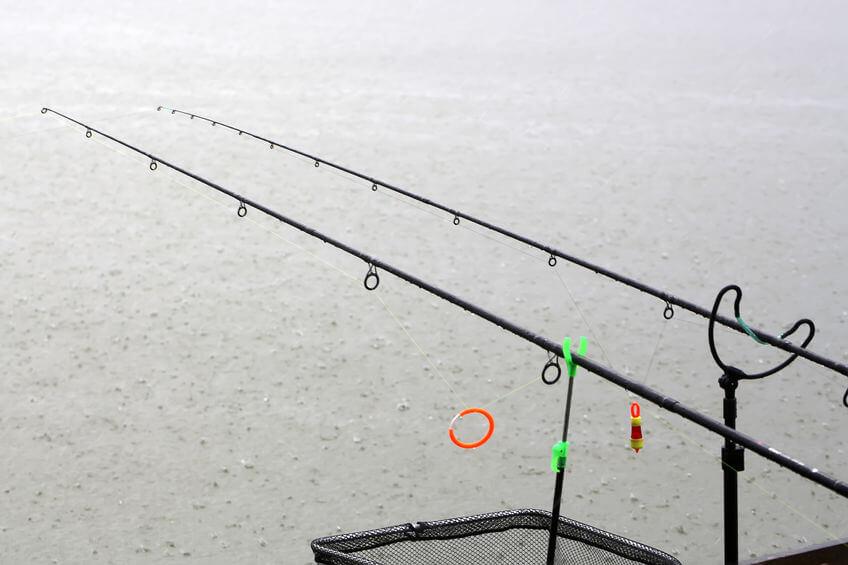 fishing rods and dip net closeup in rain