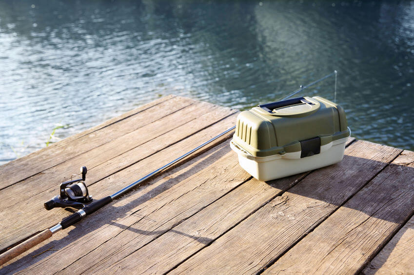 fishing tackle box and rod on wooden pier at riverside