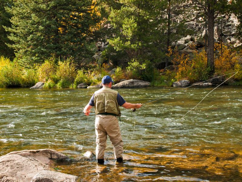 fly fisherman fishing at river