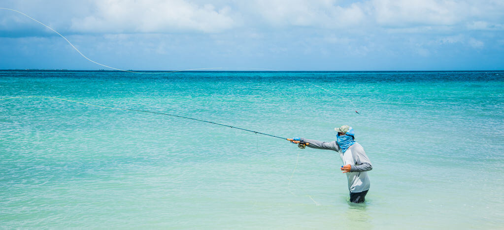 fly fisherman fishing in ocean from beach