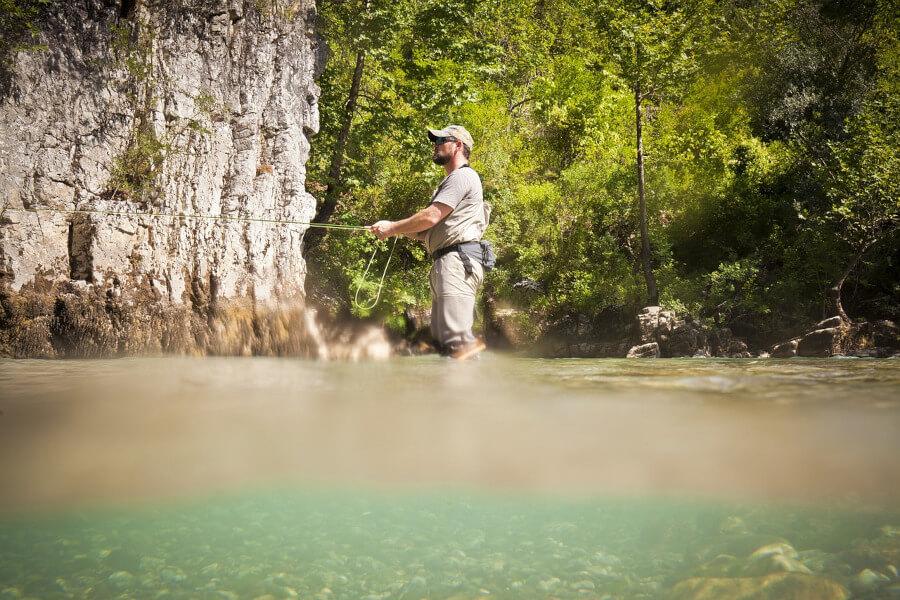 fly fisherman fishing in river