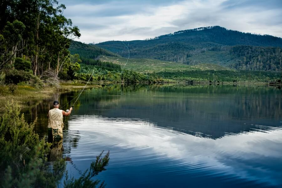 fly fisherman in brown jacket standing on river with fly rod