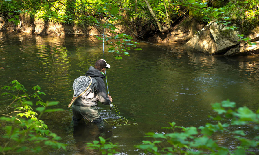 fly fisherman wearing wading boots and jacket fishing trouts in river