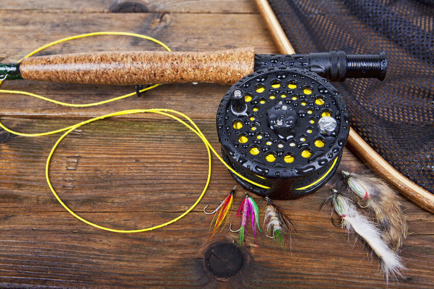 fly fishing rod and reel with different types of fishing flies
