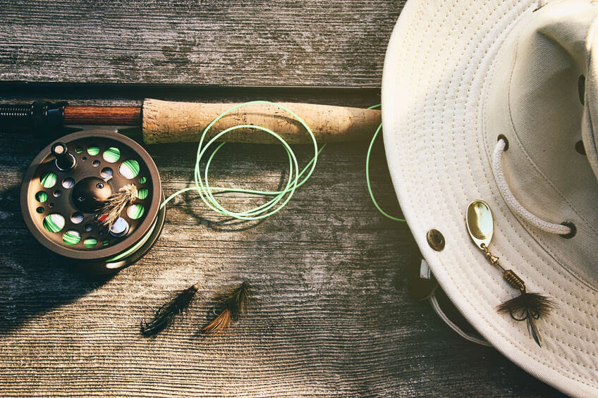 fly fishing rod with flies and canvas hat