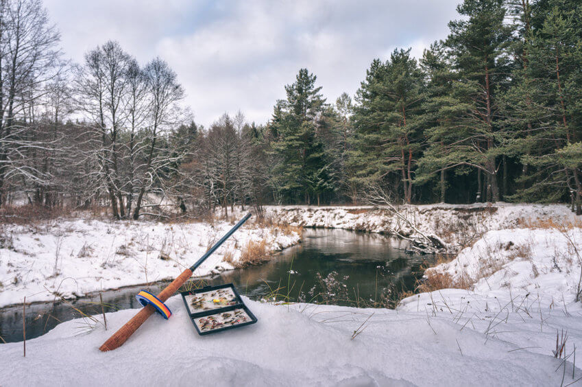 fly rod and box with flies on the bank of a winter river