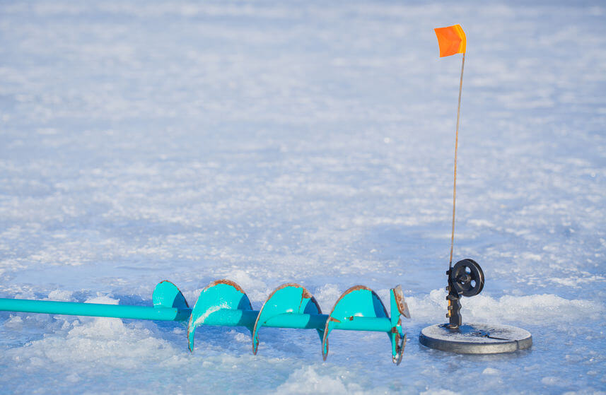 ice fishing tip up and ice auger on the winter lake
